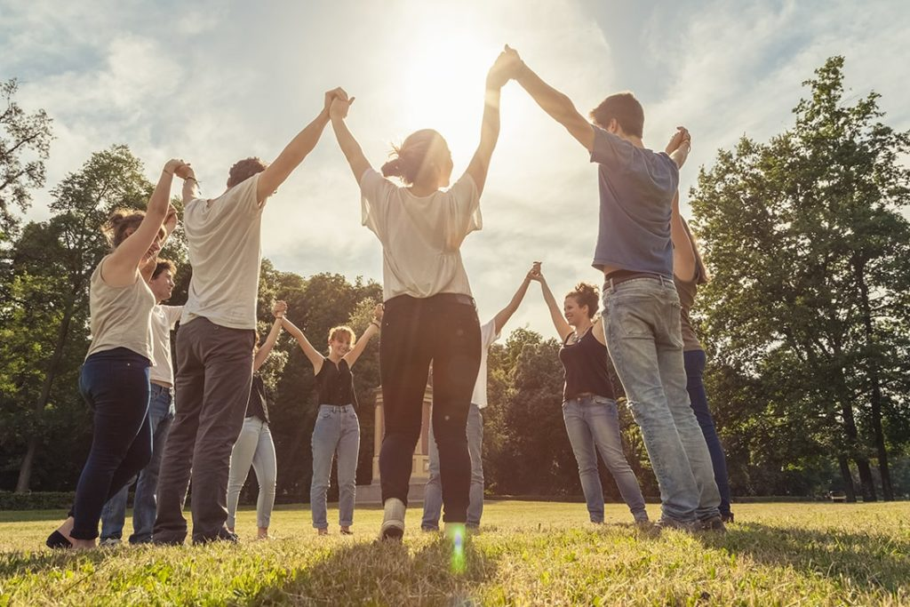 Group of friends holding hands in the grass